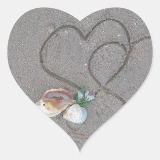 2 hjärtor i sanden med snäckor hjärtformat klistermärke