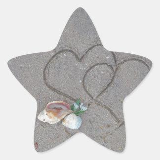 2 hjärtor i sanden med snäckor stjärnformat klistermärke