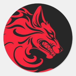 Aggressiv röd och svart stam- varg runt klistermärke
