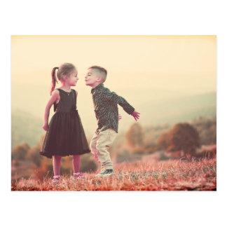 anpassadevintage som kysser ungar under solen vykort