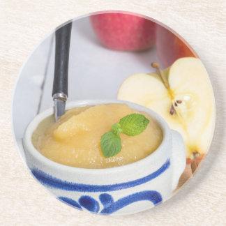 Applesauce med kanel i stengodsbunke glasunderlägg i sandsten