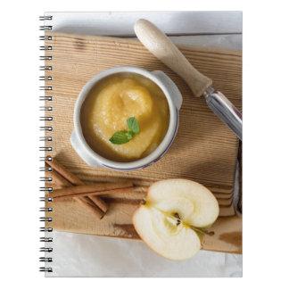 Applesauce med kanel i stengodsbunke spiralbundna anteckningsböcker