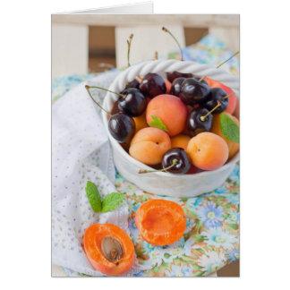 Aprikosar och körsbär i en bunke hälsningskort