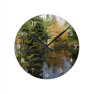 Avslappnande trädgårds- platsbild, härliga träd… rund klocka
