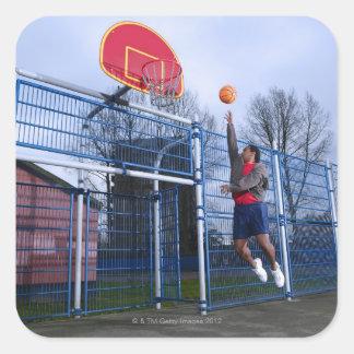 Barn bemannar att leka basket utomhus fyrkantigt klistermärke