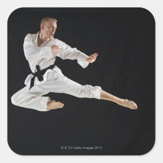Barn bemannar att utföra karate sparkar på svart fyrkantigt klistermärke