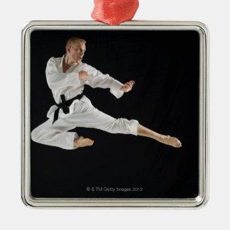 Barn bemannar att utföra karate sparkar på svart julgransprydnad metall
