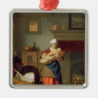 Barnflicka med bebiset i en insida silverfärgad fyrkantigt julgransprydnad
