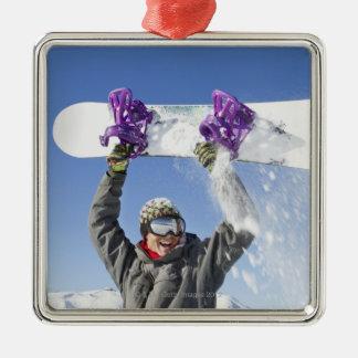 Barnmaninnehav hans snowboard ovanför hans huvud julgransprydnad metall