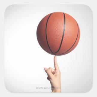 Basket på pekfingret, händernärbild fyrkantigt klistermärke