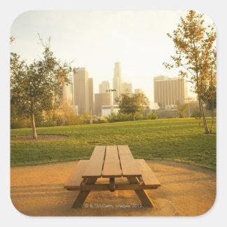 Beskåda av centra från picknick i stads- parkerar fyrkantigt klistermärke