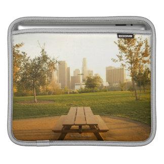 Beskåda av centra från picknick i stads- parkerar sleeves för iPads