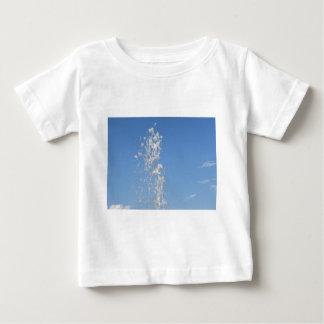 Bevattna att bespruta från en fontän mot blåtten tee shirt