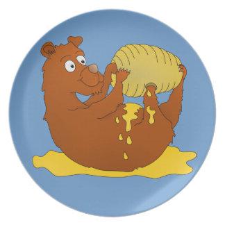 Björn som äter från en bikupa tallrik