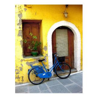 Blåttcykel mot en gul vägg vykort