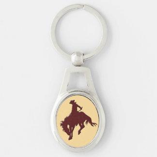 Brun guld- Cowboy som sparkar bakut hästen Ovalt Silverfärgad Nyckelring