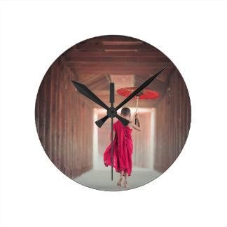 Buddistisk munk med det röda paraplyet rund klocka