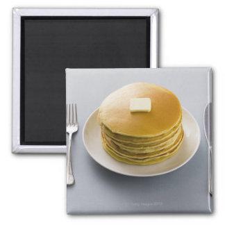 Bunt av pannkakor med smör på en plätera magnet