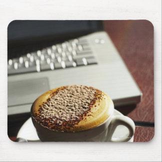 Cappuccino framme av bärbar dator musmatta