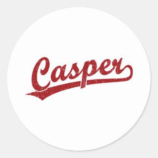 Casper skrivar logotypen i rött runt klistermärke