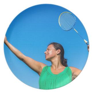 Colombiansk kvinnaserve med badmintonracket tallrik