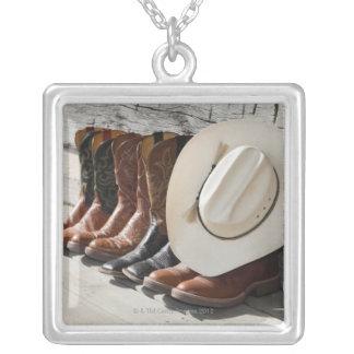 Cowboyhatten ror på av cowboykängayttersida en silverpläterat halsband