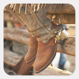 Cowboykängor på staket 2 fyrkantigt klistermärke