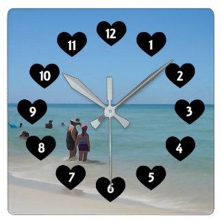 Dagen på stranden med hjärtaväggen tar tid på fyrkantig klocka