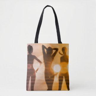 Damer på stranden med silhouetten tygkasse