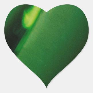 Den abstrakt kristallen reflekterar grön hjärtformat klistermärke