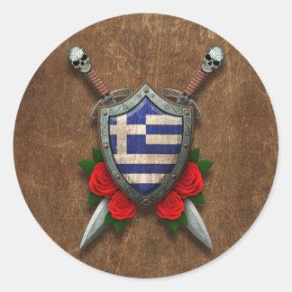 Den åldriga grekiska flagga skyddar och svärd med runda klistermärken