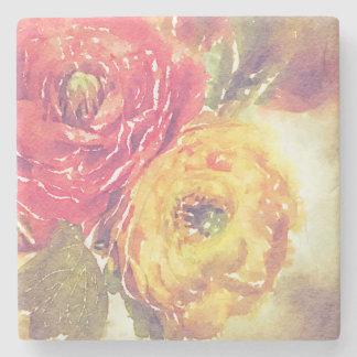 Den älskvärda röda gula ranunculusen blommar underlägg sten