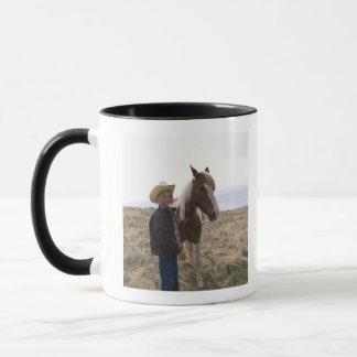 Den autentiska unga cowgirlen spänner på med mugg