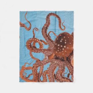 Den bruna bläckfisken på en träblått stiger ombord fleecefilt