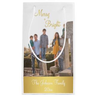 Den glada och ljusa guld- julfotogåvan hänger lös
