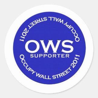 Den occupy wall street supportern knäppas runt klistermärke