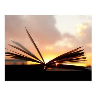Den öppna boken och solnedgången fotograferar vykort