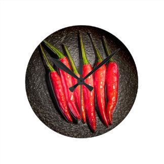 Den röda chilipepparväggen tar tid på rund klocka