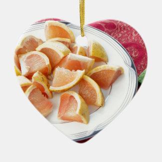 Den röda grapefrukten lappar på en runda pläterar julgransprydnad keramik