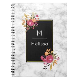 Den rosa blommigten tränga någon buketter på svart anteckningsbok med spiral