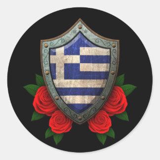 Den slitna grekiska flagga skyddar med röd ros runt klistermärke