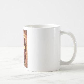 Den spartanska hjälmen rostar på bakgrund med en kaffemugg