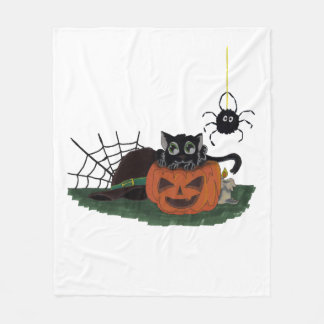 Den svart katten sitter på en jack o lantern med fleecefilt