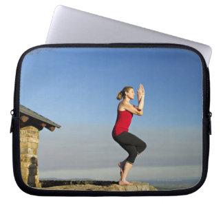 den unga kvinnan övar yoga på en bluff i laptop fodral