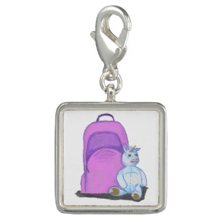 Den välfyllda unicornen sitter vid en lila skolar foto berlock