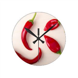 Den varma röda chilien pepprar på ett ljust trä rund klocka