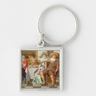 Elegantfigurer som festar på ett bord fyrkantig silverfärgad nyckelring