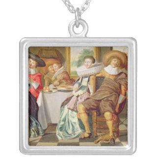 Elegantfigurer som festar på ett bord silverpläterat halsband