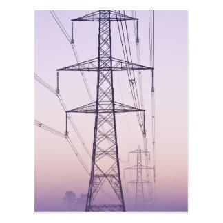 Elektricitetspylons i mist på dawn.en vykort