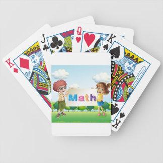 En flicka och ett pojkeinnehav en mathsignage spelkort